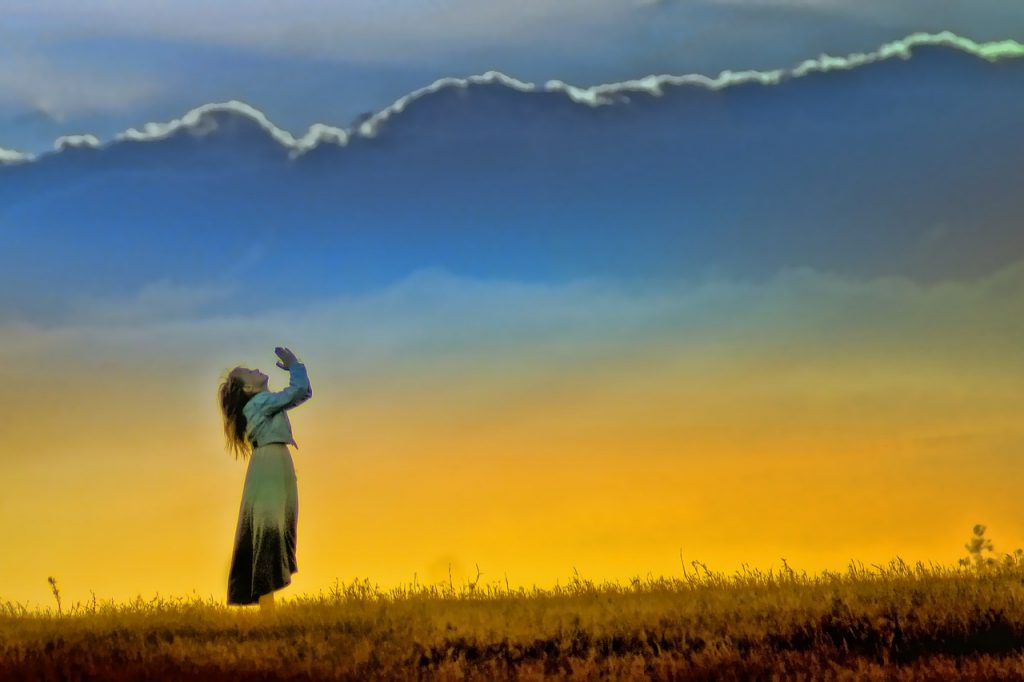 woman praying, standing and looking toward the sky with pleading posture