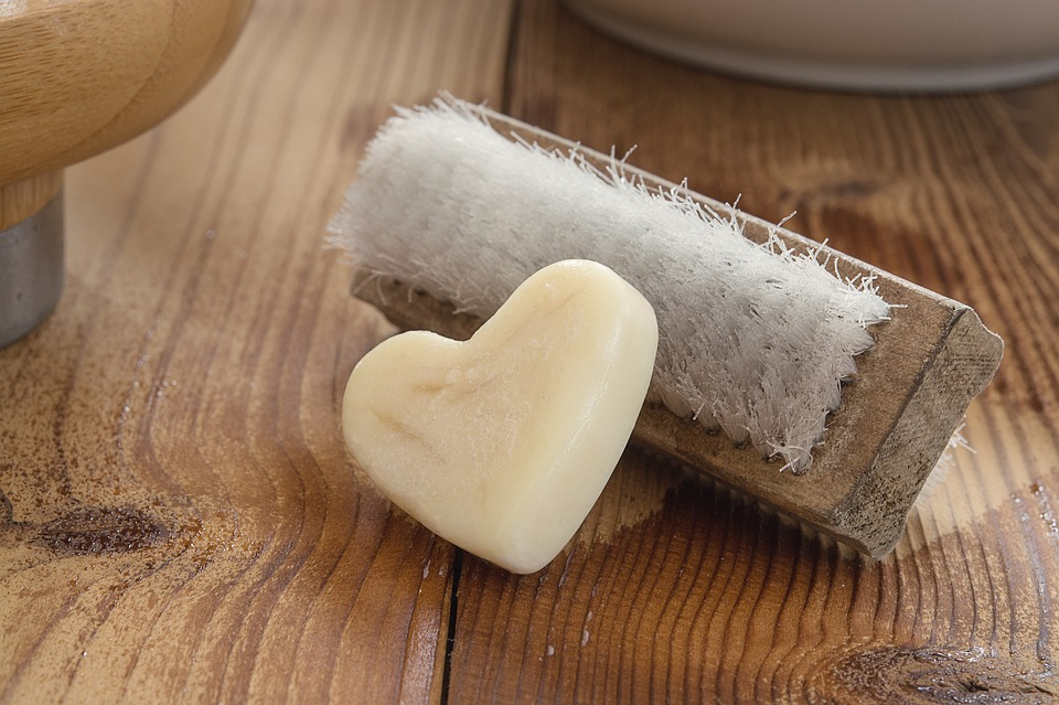 soap in the shape of a heart and a brush nestled together for cleaning
