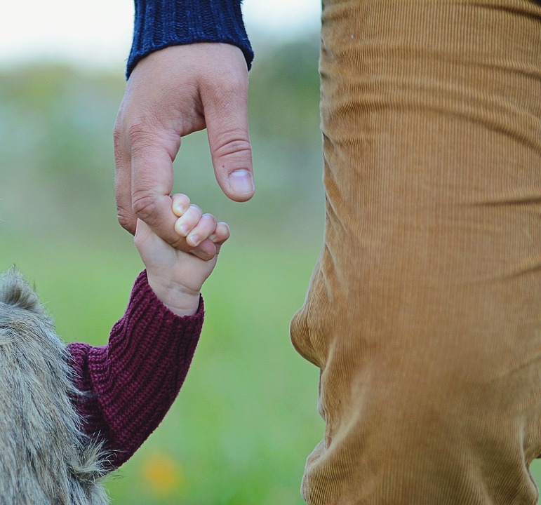 Parent holding hand with child (child grasping tightly to the finger)