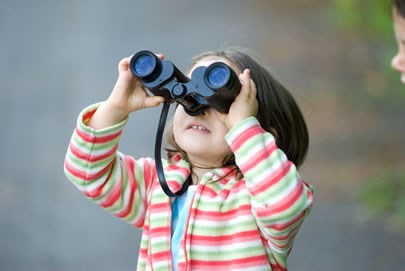 little girl looking at the sky through binoculars
