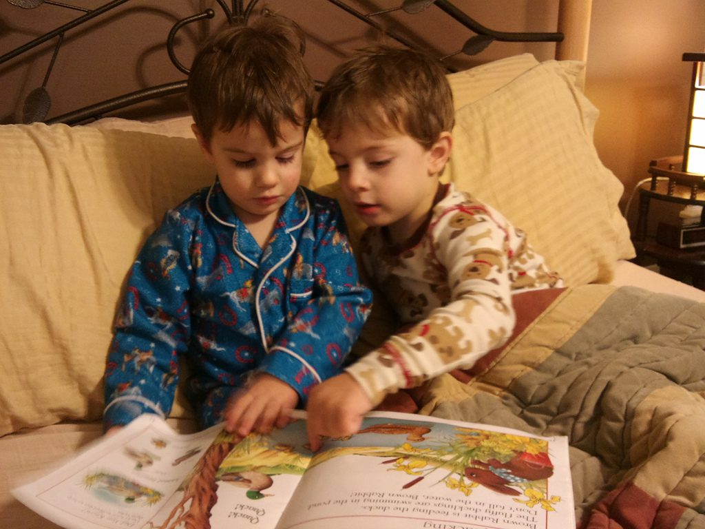 two young boys reading a story book together