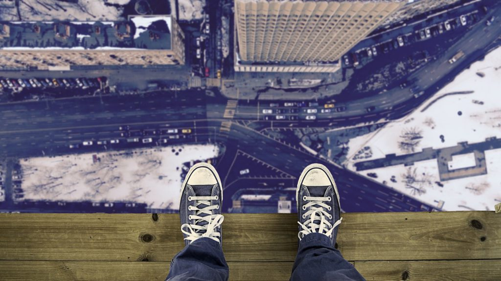 standing on a ledge, looking down at feet and to the street below