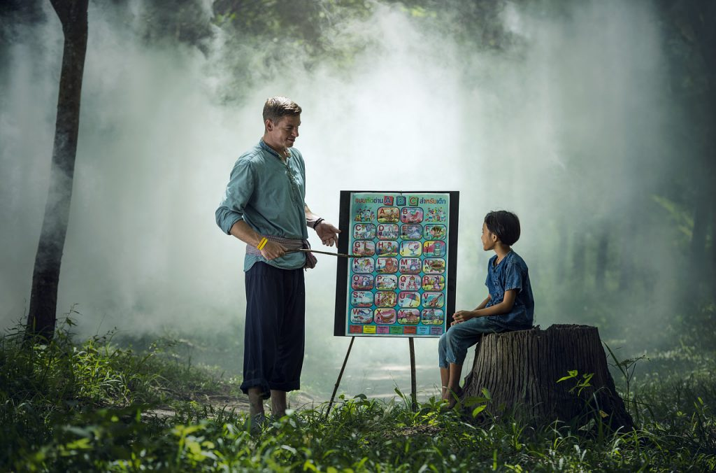 Teacher teaching young boy pointing to a chart