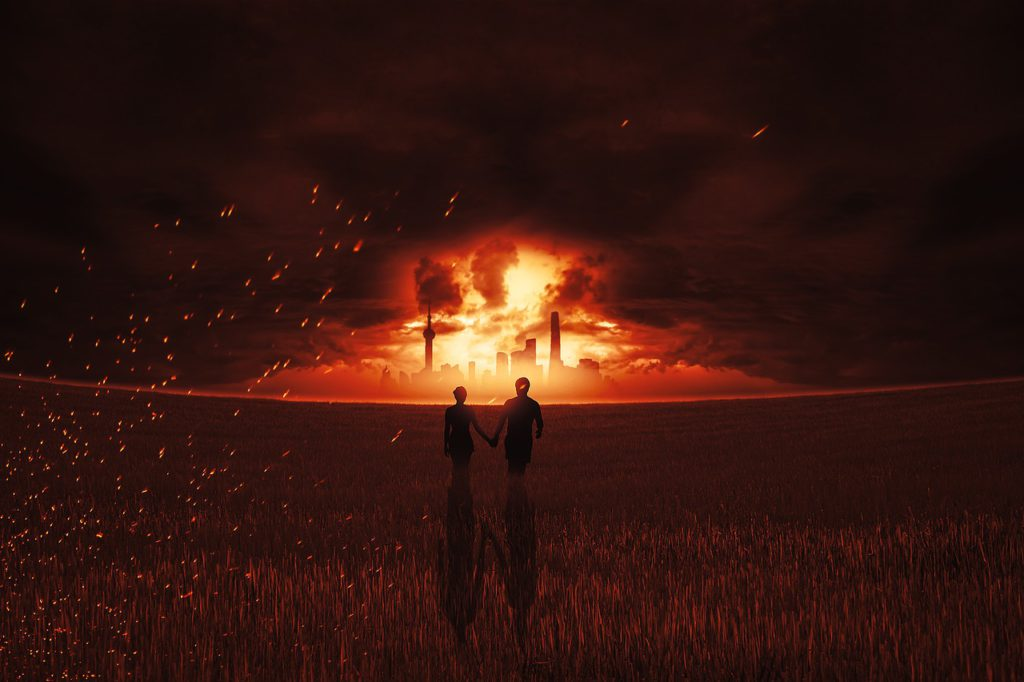 Two people holding hands, at night, looking at what looks like an explosion in a city in the distance ahead of them