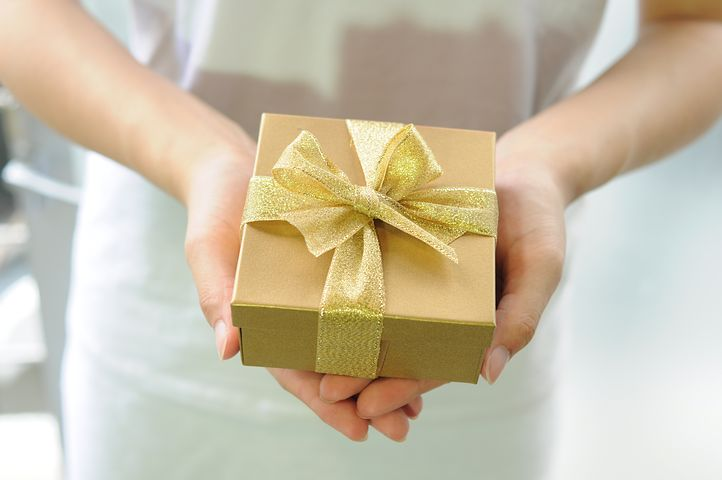 hands holding a gift wrapped in gold paper with gold lace bow