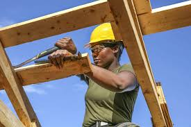 construction site picture showing person in hard hat cutting wood