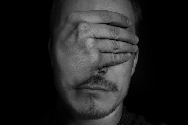 Man covering his eyes with his hands as if perplexed