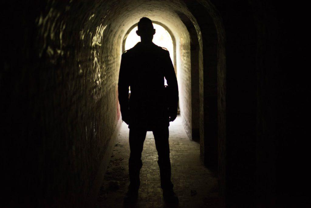 Man standing, facing a door open with light streaming in