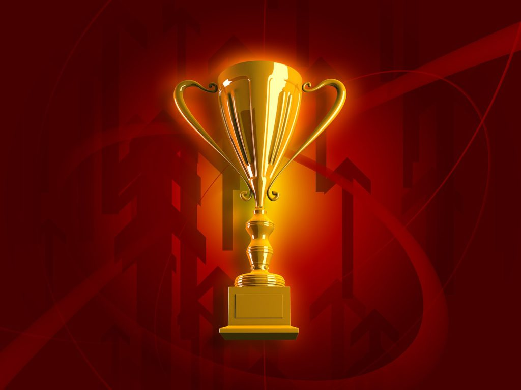 golden trophy with light shining on it against red backdrop with lots of arrows pointing upward