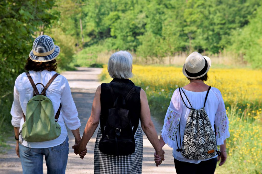 3 women walking with purpose down a path with back packs, holding hands