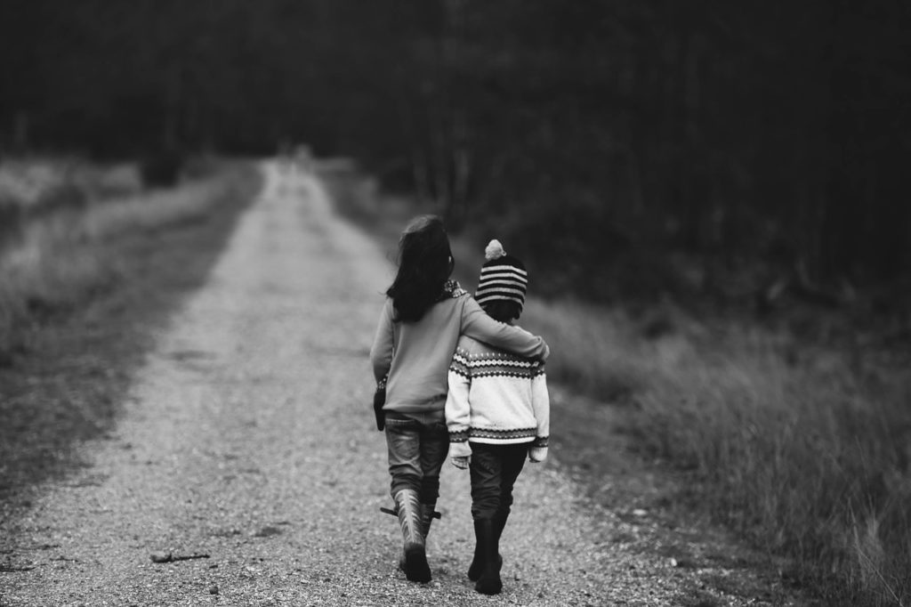 black and white pic of two children walking down the street, one with their arm around the other