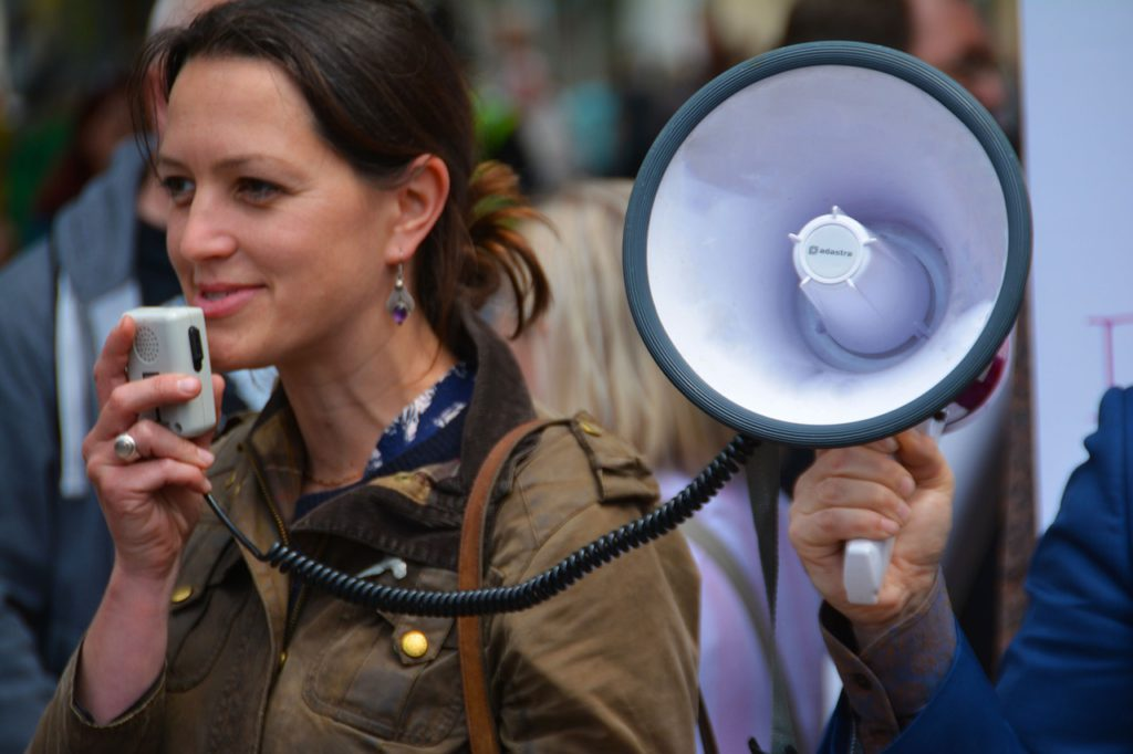woman holding and speaking into a hand held loud speaker