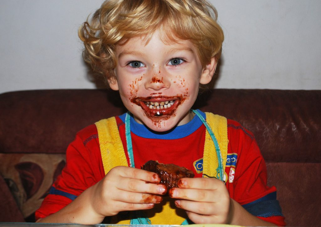 Young boy with a big chocolate face grin with a piece of melting chocolate in his hands