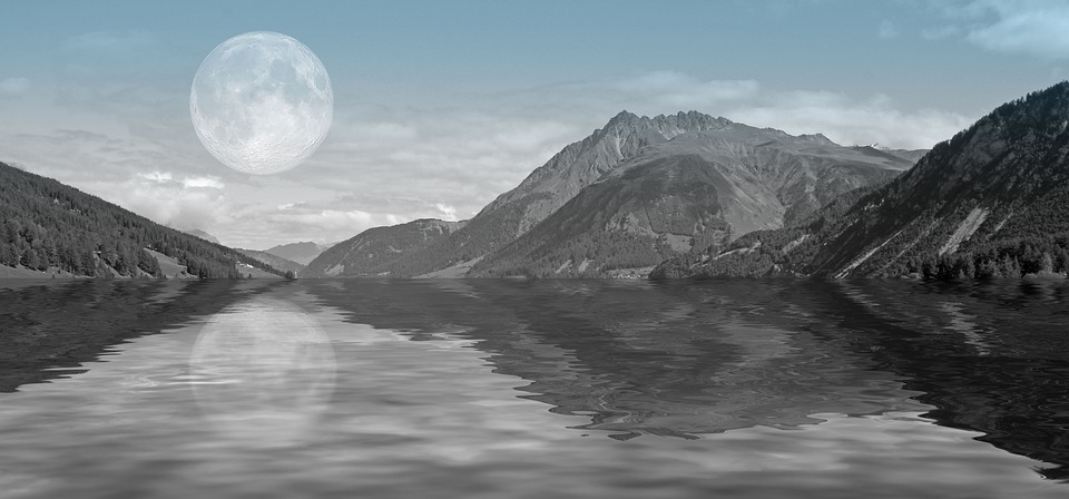 mountains and river with big moon reflecting in water