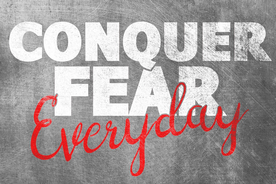 Conquer Fear Everyday - white and red lettering on gray background
