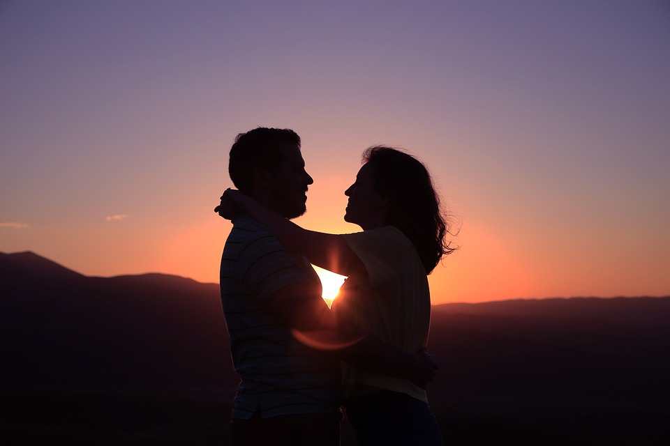 a man and woman in light embrace, facing each other, with a sunset behind them