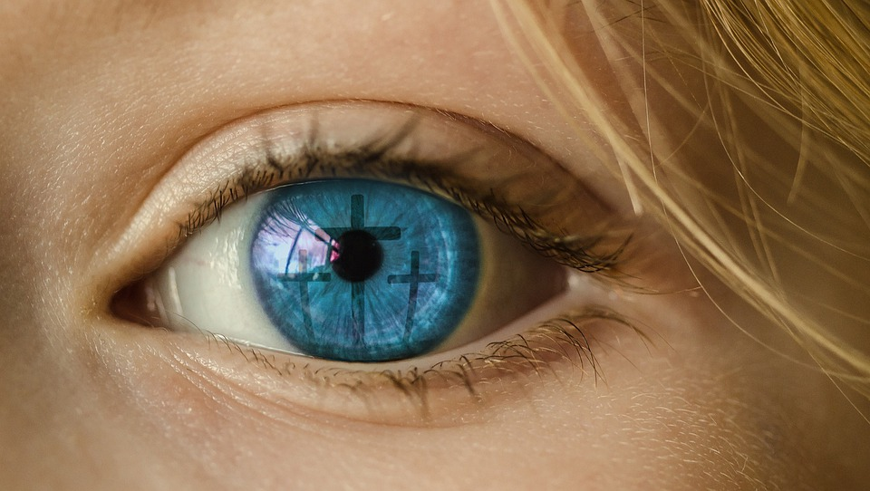 Close up of an eye with a reflection of 3 crosses in the iris