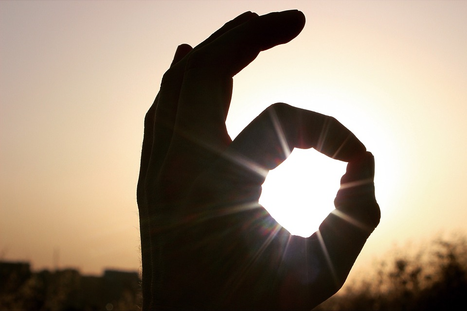 """Hand doing the """"ok"""" sign, with sunlight streaming from behind, right in the circle of the O."""