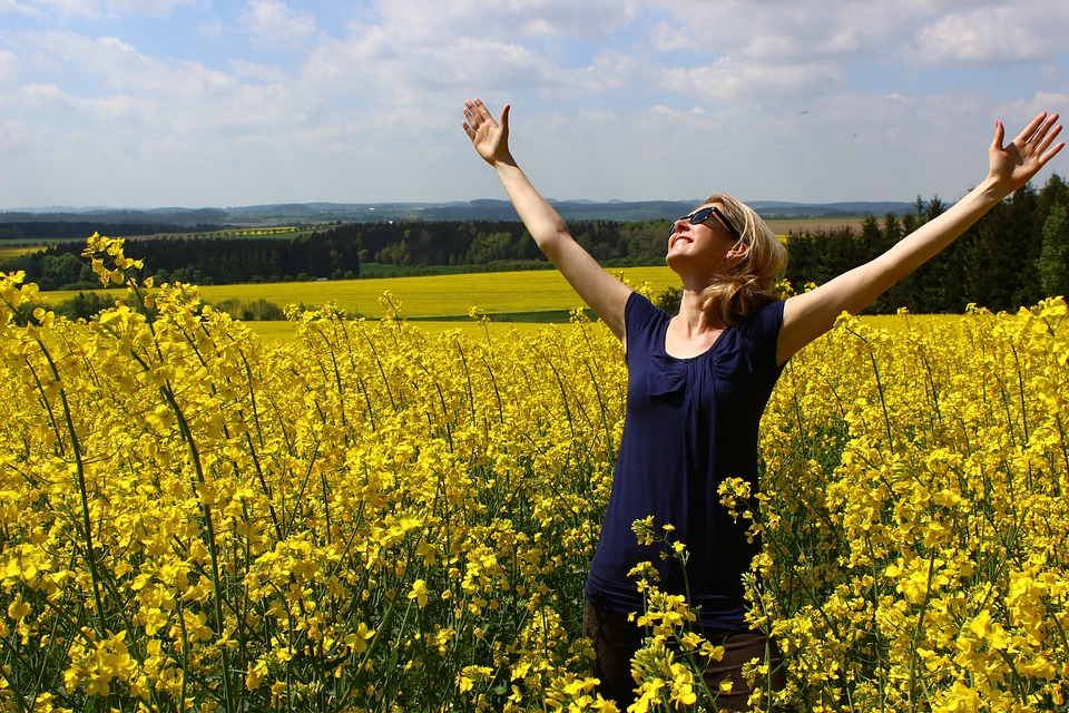 woman reaching her arms up, looking up, praising, in field of yellow flowers