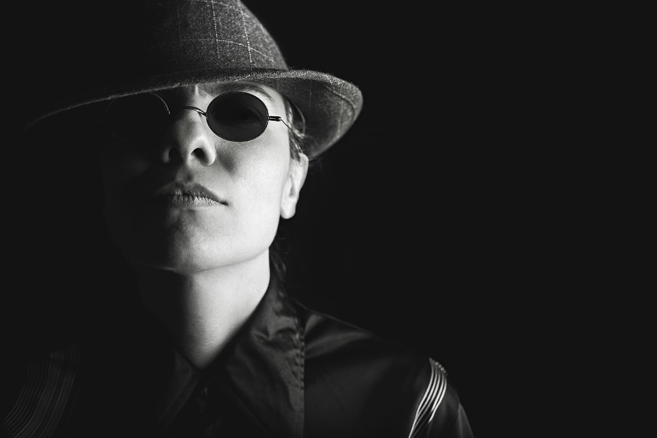 spy with dark glasses and hat against black background