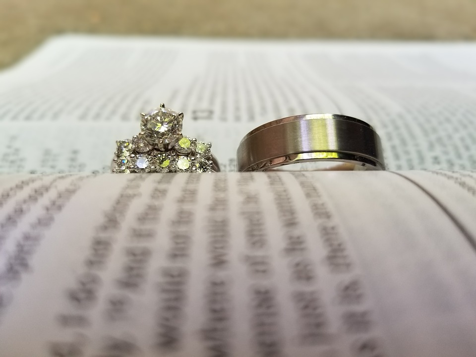 two wedding rings in sitting on an open page with words blurred out