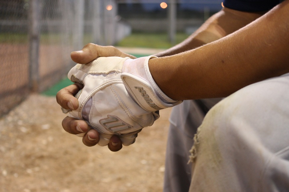baseball player sitting on the bench behind the fence, batting gloved hands crossed on knees