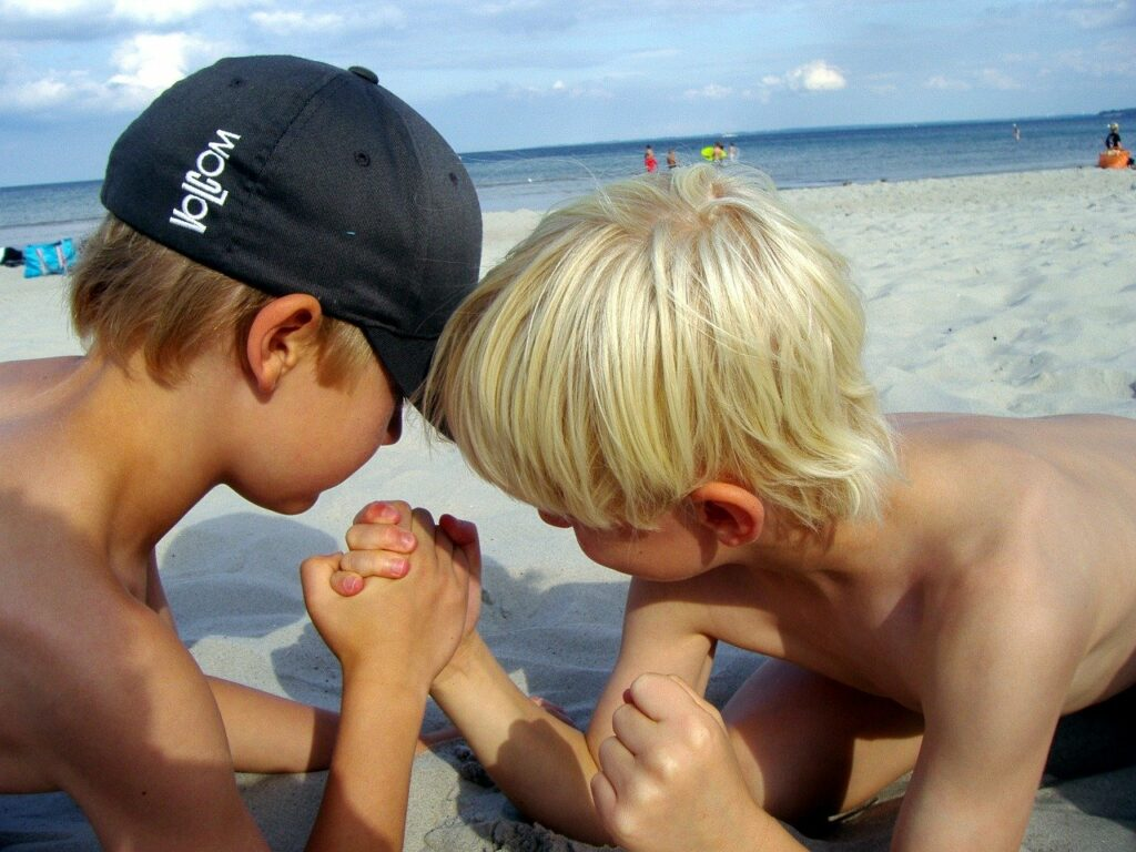 two young boys arm-wrestling in the sand