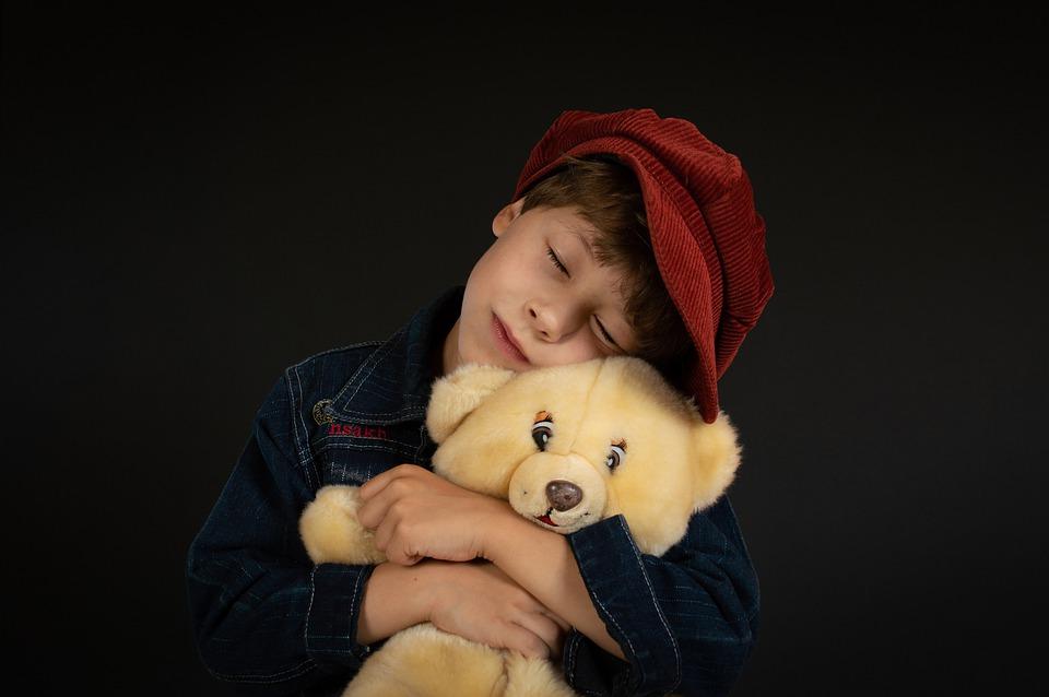 a boy hugging his teddy bear