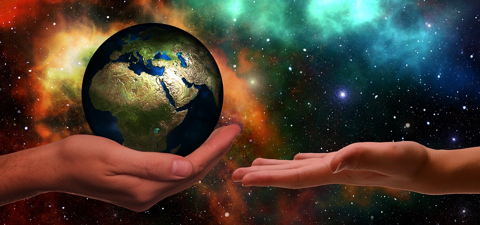 One hand holding the globe as if to pass it over to the other hand