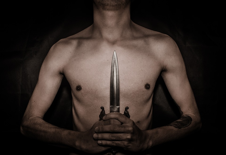 bare chested man holding a dagger in front of him