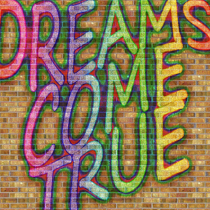 """Graffiti like letters on a brick wall background that say: """"DREAMS COME TRUE"""""""