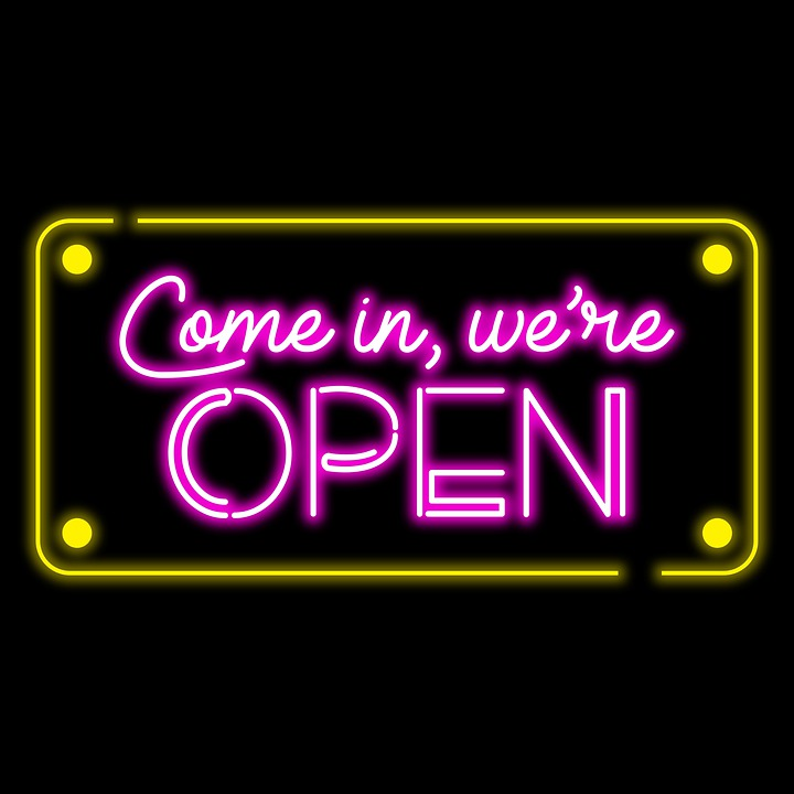 """Neon sign that says, """"Come in, we're OPEN"""""""
