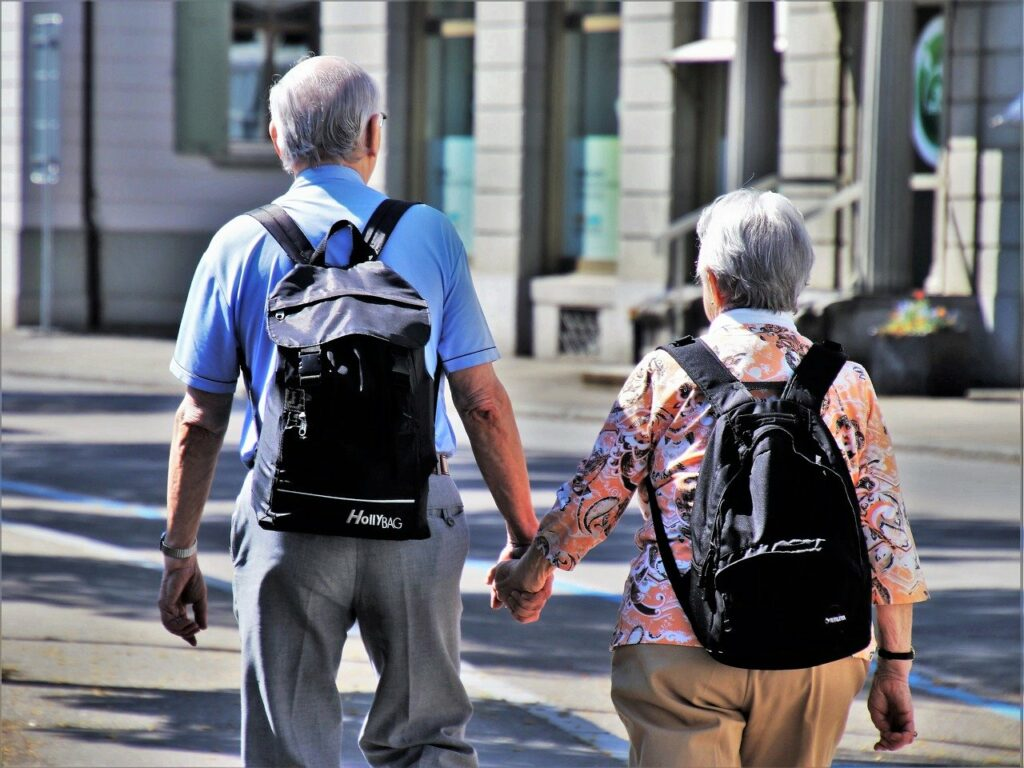 A gray-haired couple walking away from camera with back packs, holding hands
